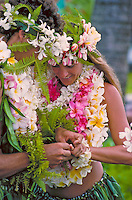Couple getting married in Hawaii with flowers leis and ti leaf skirts share a close moment.