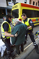 Switzerland. Canton Ticino. Lugano. Day scene for a medical emergency intervention. An elderly man with gray hair fell on the ground and has hurt himself badly. The aged man needs to be brought by ambulance to hospital for a medical examination. Two paramedics wear blue uniforms  and medical gloves. Both work for the Croce Verde Lugano and are professional certified nurses. The Croce Verde Lugano is a private organization which ensure health safety by addressing different emergencies services and rescue services. Medical gloves are made of different polymers including latex, nitrile rubber, polyvinyl chloride and neoprene. 28.01.2018 © 2018 Didier Ruef