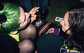 London, England. Young women from above, one with green hair, one with nose ring, boots with bouncing soles, Stella Artois Marlborough Lights crushed.