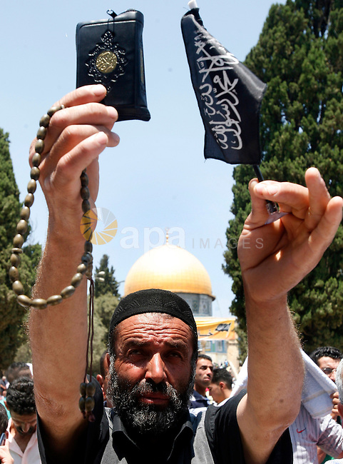 A Palestinian worshiper holds the holy Qur'an outside the Dome of the Rock at the al-Aqsa mosque compound in Jerusalem during the third Friday prayers of the Muslim holy month of Ramadan on 03 August 2012. Muslims fasting in the month of Ramadan must abstain from food, drink and sex from dawn until sunset. Photo by Mahfouz Abu Turk