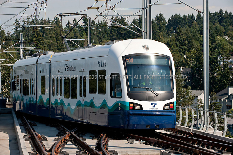 "7/28/2009--Seattle, WA, USA..A Sound Transit Link train pulls arrives at the Tukwila Station, south of Seattle..The Sound Transit Link Light Rail opened in Seattle on July 20th 2009, after decades of planning and political wrangling. Construction of the city's new mass transit system took five years and cost $2.3 billion. By the end of the 2009 Sound Transit says light rail will reach Sea-Tac Airport; the train currently runs 14 miloes from the downtown Westlake station to Tukwila, south of Seattle, with extensions planned to run north and east out of the city.The first efforts to build modern rail transit in the Seattle area began about 50 years ago. A comprehensive plan was defeated by voters three times (1968, 1970, 1995), and then a shortened, ""starter"" system was passed in 1996. ..©2009 Stuart Isett. All rights reserved."