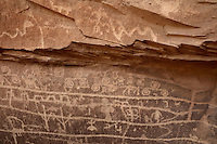 Petroglyphs, images etched into the rock face, by the Basketmaker people, 500-750 AD, at the Ismay Rock Shelter in the Canyons of the Ancients National Monument, Colorado, USA. The Basketmaker were pre-Puebloan people who lived in this area from 1500 BC. The rock shelter itself consists of a sleeping area underneath a rock overhang, whose surfaces are covered with petroglyphs including animals, spirals and long scribe lines. The Canyons of the Ancients National Monument encompasses most of the Hovenweep National Monument and protects over 6000 archaeological sites. Picture by Manuel Cohen