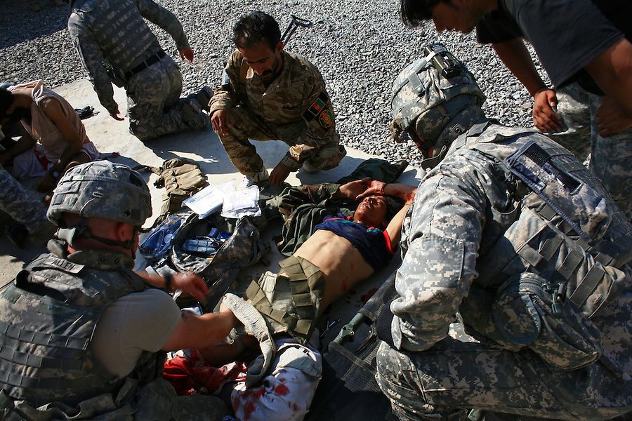 Soldiers from Alpha Battery 3-321 Field Artillery in Afghanistan's eastern Khost Province treat two Afghan guards wounded when a suicide bomber detonated his vest at the entrance to the battery's outpost at the Terezayi District Center near the Afghan-Pakistan border on Thursday Oct. 16, 2008.