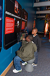 Oakland CA 3rd grade boys on school field trip to Chabot Space and Science Center studying touch screnn that deals with solar system exploration
