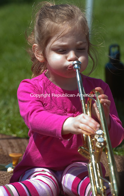 WOODBURY, CT 27 APRIL 2013--042713JS87--FOR COUNTRY LIFE USE ONLY- At the Southbury Music Studio tent, Lyla Waychowsky, 3, of Woodbury, tries her best to play the trumpet during the 19th annual Earth Day celebration at Hollow Park in Woodbury. The nonprofit event sponsored in part by New Morning Market, included entertainment and local, natural and organic vendors and exhibitors. Any proceeds raised during the event will be donated to local charities. .Jim Shannon Republican-American.