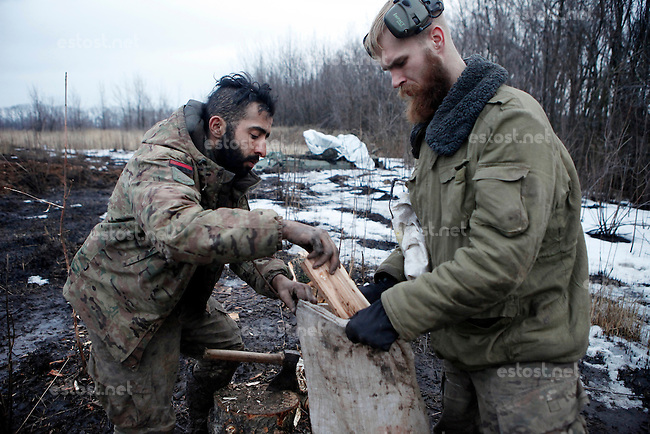 "UKRAINE, 02.2016, Oblast Donetsk. Ukrainian-Russian conflict concerning Eastern Ukraine / Foreign volunteers (""Task Force Pluto"") fighting with the far-right militia Pravyi Sektor against the Russian-backed separatists: Ben (Austria) and Craig (USA) fill a bag with wet fire wood for their trench positions close to the Donetsk frontline. © Timo Vogt/EST&OST"