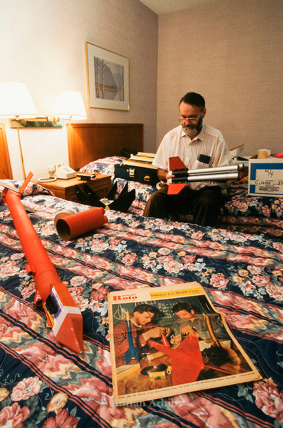 Paul Esterlee preparing his rocket in the Best Western Inn in Manchester Tennessee the night before a mass rocket launch.  In the foreground a magazine featuring himself making a rocket when he was 16 years old.