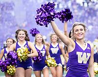 Husky cheerleaders lead the team onto the field.