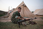 29/06/2014. Khanaqin, Iraq. A Kurdish peshmerga fighter sits with his AKM assault rifle at a Kurdish peshmerga base in Khanaqin, Iraq.<br /> <br /> The peshmerga, roughly translated as those who fight, is at present engaged in fighting ISIS all along the borders of the relatively safe semi-automatous province of Iraqi-Kurdistan. Though a well organised and experienced fighting force they are currently facing ISIS insurgents armed with superior armament taken from the Iraqi Army after they retreated on several fronts. &copy; Matt Cetti-Roberts