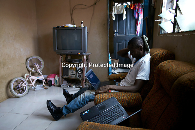 "ACCRA, GHANA APRIL 19: A romance scammer known as ""Ghost"" works on his laptop in a house on April 19, 2015 in Zongo area of Accra, Ghana.  He is one of many young unemployed men here who is involved in Romance scams, credit card fraud and etc. The country is a center for different online scams. Both men and women are lured to send cash to someone they only met on the net.  Due to limited opportunities, many youngsters spend their days in Internet cafes trying to scam people form all over the world. (Photo by: Per-Anders Pettersson)"