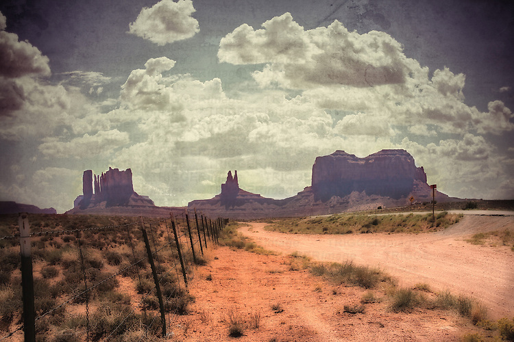 Large monolithic rocks in the background looking through Monument Valley in the United States, with desertic road and clouds in a blue summer sky with a level of texture