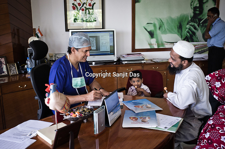 58 year old heart surgeon, Dr. Devi Prasad Shetty speaks with a family during OPD in his office at the Narayana Hrudayalaya in Bangalore, Karnataka, India. Photo: Sanjit Das/Panos
