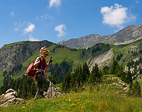 CHE, SCHWEIZ, Kanton Bern, Berner Oberland, Engstlenalp am Ende des Gentals: Frau wandert mit Rucksack und Wanderstoecken | CHE, Switzerland, Bern Canton, Bernese Oberland, Engstlenalp at Gen Valley: woman hiking with rucksack + hiking sticks