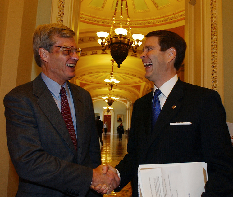 Sens. Bill Frist, R-Tenn., right, and Max Baucus, D-Mont, share a laugh on their way to a news conference to discuss the passage of the Medicare Bill.