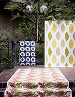 Interior of Barbican conservatory. A tiled floor, with a small step leading up, is the foreground of this image. Upon the tiles and draped over the step, lies a large piece of fabric with a floral, geometric pattern. Towards the background, two other pieces of fabric stand against a black railing. The left side one is small with a geometric pattern of red leaves, each surrounded by a blue circle. The fabric on the right is bigger in height and width. It has a geometric pattern of green, large leaves. Behind the railing stands a street light with two globe bulbs. There also plants and large leaves behind the railing. The image is light and gives a feeling of a large, airy interior.