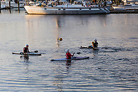 A soccer ball flies between three guys in three kayaks playing among the boats moored at the San Leandro Marina.