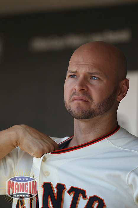 SAN FRANCISCO - AUGUST 25:  Cody Ross of the San Francisco Giants gets ready in the dugout during the game against the Cincinnati Reds at AT&T Park on August 25, 2010 in San Francisco, California. Photo by Brad Mangin