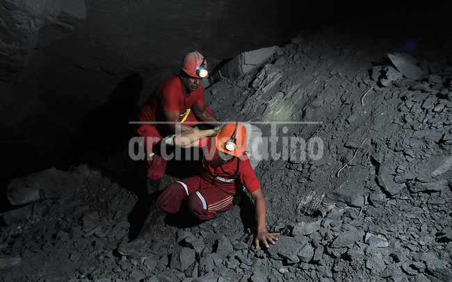 Minners working in  in a tunnel 1,500 feet under ground in a gold mine near Segovia, Antioquia department, Colomb ia
