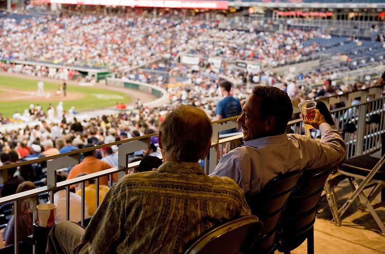 UNITED STATES - JULY 14: Rep. Mel Watt, D-N.C., right, and his college roommate Marvin Mood, watch the 50th Annual Congressional Baseball Game at Nationals Park.  The Democrats prevailed over the Republicans by the score of 8-2.  (Photo By Tom Williams/Roll Call)