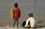 Two boys on the banks of the River Ganges near to the Sangam where the Ganges,Yamuna and Saraswati Rivers meet. It was estimated that 30 million people visited the Maha Kumbha Mela in 1989 making it the largest gathering of any kind in modern history. Maha Kumbha Mela is held every twelve years at Prayag Allahabad in Uttar Pradesh in India.