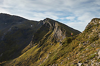 Female hiker hikes on narrow trail towards distant summit of Matmora mountain peak, Austvågøy, Lofoten Islands, Norway