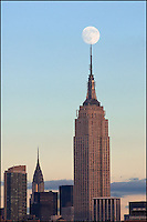Empire State Building with a full moon on top at sunset.