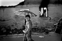 An Albanian boy, with an umbrella to protect himself from the heat walks through the  ruins of Mitrovice. .June 22nd, Kosovo.