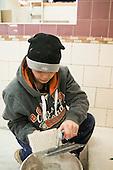 Tiling student applying adhesive to a tile, Able Skills, Dartford, Kent.