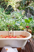 An outdoor bath filled with floating flowers on a secluded deck at the Maia Luxury Resort & Spa