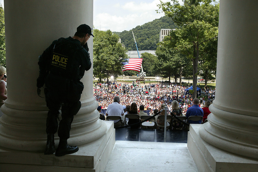A secret service agents watches from behind a pillar as President George W Bush makes remarks on the steps of the West Virginia State Capitol in celebration of the Fourth of July, Sunday, July 4, 2004, in Charleston, W.Va..Photo by Brooks Kraft/Corbis