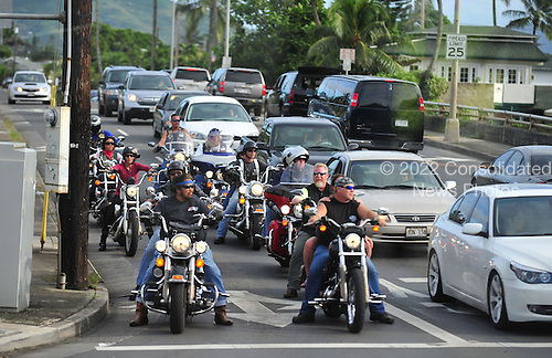 United States President Barack Obama's motorcade passes a group of motorcyclists stopping at a light in Kailua, Hawaii as the President heads to play tennis on Saturday, January 1, 2011. .Credit: Cory Lum / Pool via CNP