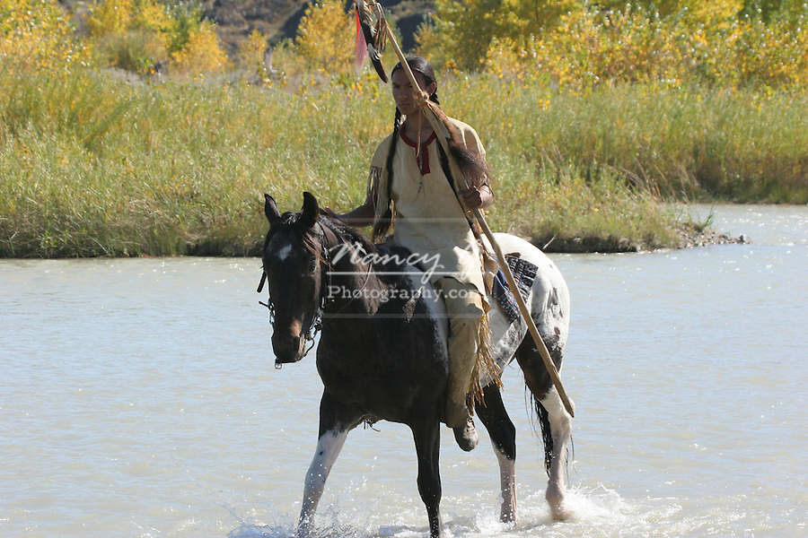 A Native American Sioux Indian boy on horseback walking through a river scouting