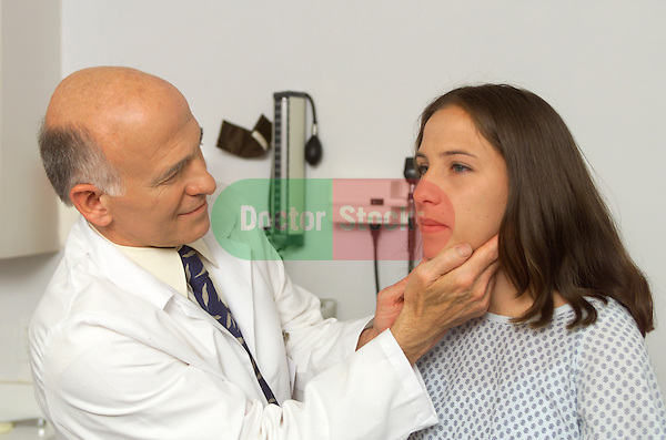 older male doctor examining glands of adolescent girl with fingers
