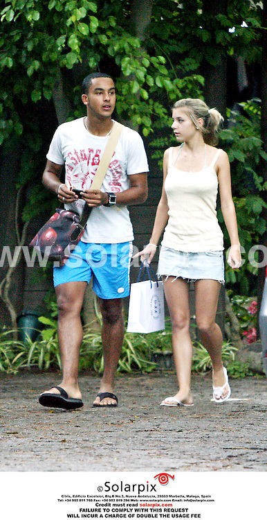 ALL ROUND EXCLUSIVE PICTURES BY SOLARPIX.COM.Arsenal FC wonder kid Theo Walcott and girlfriend Melanie Slade brave the rain on a shopping trip in  Spain after the world cup on short brake on the Costa del Sol..Job ref AB1 2582 14.7.06
