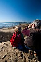 Couple watches Northern Elephant Seals (Mirounga angustirostris) [Wild] from Sand Dunes, Ano Nuevo State Park (formerly Ano Nuevo State Natural Preserve), San Mateo County, California, United States of America, with the largest mainland USA northern elephant seal breeding colony