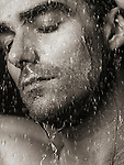 Sensual closeup portrait of a man face with closed eyes under pouring rain or shower water Black and white sepia toned