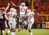 Ohio State defensive players including Ohio State Buckeyes safety Tyvis Powell (23), defensive lineman Tyquan Lewis (59), and cornerback Gareon Conley (8) celebrate a tackle during the first quarter of the NCAA football game against the Virginia Tech Hokies at Lane Stadium in Blacksburg, Virginia on Sept. 7, 2015. (Adam Cairns / The Columbus Dispatch)