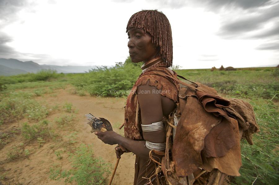"""femme Hamer pres de la frontiere avec le Nord Kenya. Elle revient du village voisin (20 km) avec des braises dans la main car son feu s""""est éteint"""