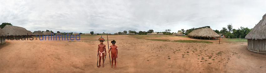 Xingu Indian boys with weapons in their village square, Amazon Basin, Brazil