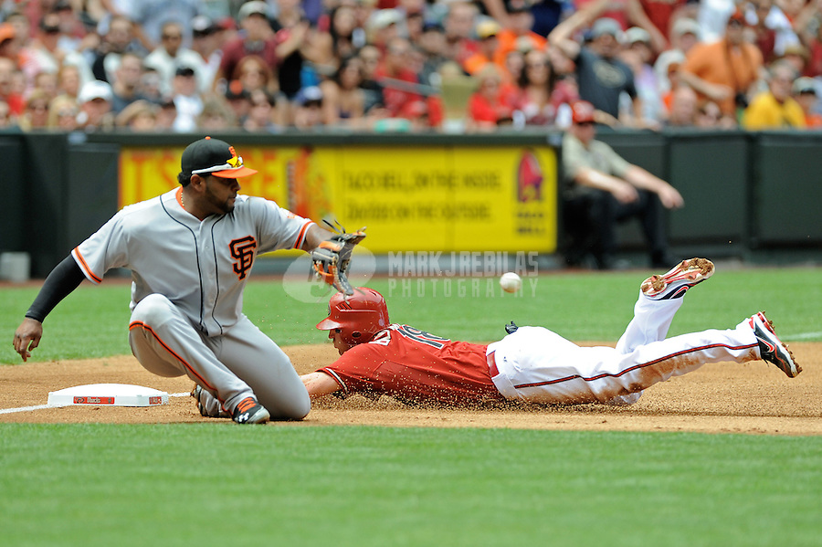 Apr. 8, 2012; Phoenix, AZ, USA; Arizona Diamondbacks base runner Willie Bloomquist slides safely into third base ahead of the tag by San Francisco Giants third baseman Pablo Sandoval in the first inning at Chase Field. Mandatory Credit: Mark J. Rebilas-