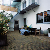 A table and bench seats are set out on a paved terrace area. A metal staircase leads to a balcony above