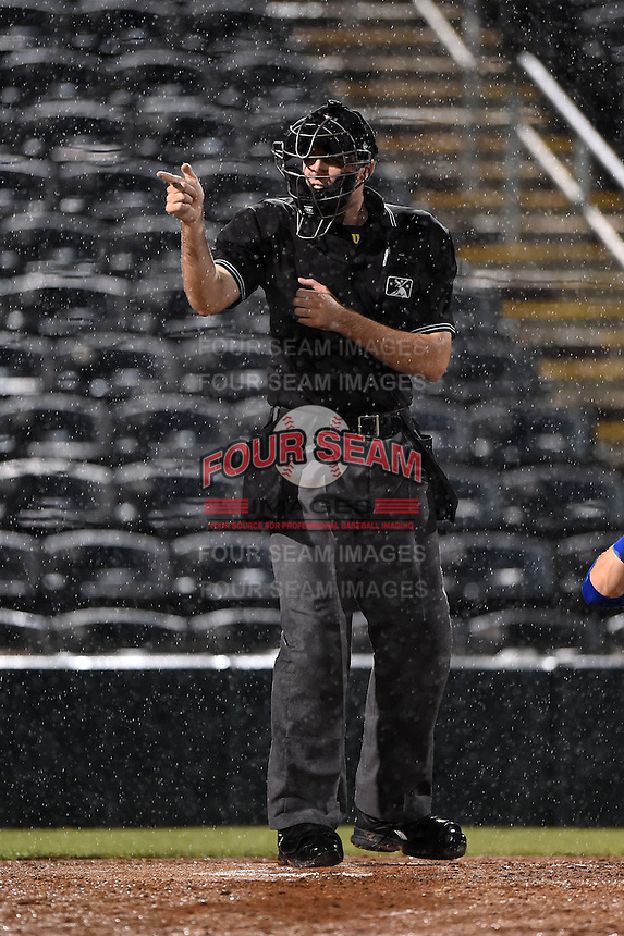 Home plate umpire Nate Tomlinson makes a call in the pouring rain during a game between the St. Lucie Mets and Fort Myers Miracle on April 18, 2014 at Hammond Stadium in Fort Myers, Florida.  St. Lucie defeated Fort Myers 15-9.  (Mike Janes/Four Seam Images)