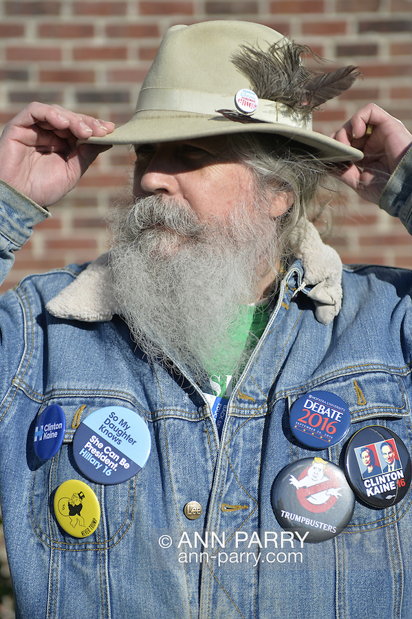 """Merrick, New York, USA. October 23, 2016. FRED S. CHANDLER, 66, of North Bellmore, wearing several political campaign buttons supporting Democratic presidential candidate Hillary Clinton, holds onto his hat in wind while attending rally to demand public water and stop New York American Water (NYAW) rate hike. His hat button was: """"Still love Bernie. Voting for Hillary."""" On denim jacket included buttons for Hofstra University DEBATE 2016 - and """"So My Daughter Knows She Can Be President. Hillary 16"""" - """"TRUMPBUSTERS"""" - """"CLINTON KAINE 16"""" - and Monopoly Man character with """"NEVER TRUMP"""" text."""