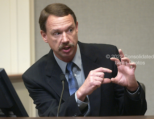 Bureau of Alcohol, Tobacco and Firearms (ATF) forensic chemist Edward C. Bender gestures during his testimony in the trial of sniper suspect John Allen Muhammad, in courtroom 10 at the Virginia Beach Circuit Court in Virginia Beach, Virginia on November 5, 2003.<br /> Credit: Dave Ellis - Pool via CNP