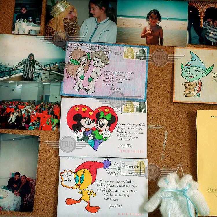 Photographs and letters pinned to the wall of a family cell at Alcala de Guadaira prison. Amaya Encarnacion shares the cell with her young daughter Maria, and the letters are from Maria's father, who is incarcerated in another prison. More than 200 women live with their children in Spanish jails. Children can live with their mothers in prison up to the age of three.