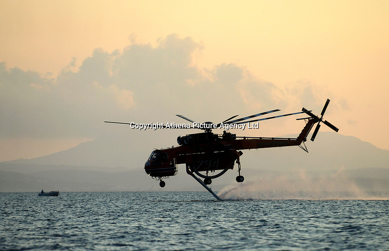 Pictured: A fire helicopter draws water from the nearby sea.<br /> Re: A forest fire has been raging in the area of Kalamos, 20 miles north-east of Athens in Greece. There have been power cuts, country houses burned and children camps evacuated from the area.