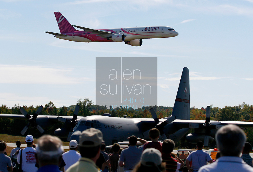 A Delta 757, painted with a pink theme to raise awareness to the fight against breast cancer, flies over a C-130 aircraft at The Great Georgia Airshow at Falcon Field Airport in Peachtree City, Ga. on Sunday, Oct. 15, 2006.<br />
