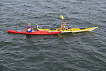 South Merrick, New York, USA. 24th May 2015. A young man and woman are laughing as they kayak in Merrick Bay along the south shore of Levy Park & Preserve during the Memorial Day Weekend. The red kayak had Carolina and the yellow kayak had Montauk written on their bows.