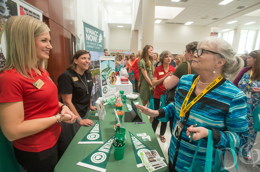 NWA Democrat-Gazette/BEN GOFF @NWABENGOFF<br /> Kellie Reynolds (from left) and Michelle Cook from Northwest Arkansas Community College talk to Gail Kinnaird, a teacher at Southwest Junior High, Thursday, Aug. 9, 2018, during the 52nd Annual Sam's Furniture Springdale Teacher Appreciation Day at Springdale High School. More than 85 vendors set up to provide information and more than $40,000 in gifts and prizes to some 2,000 teachers and staff of Springdale Public Schools.