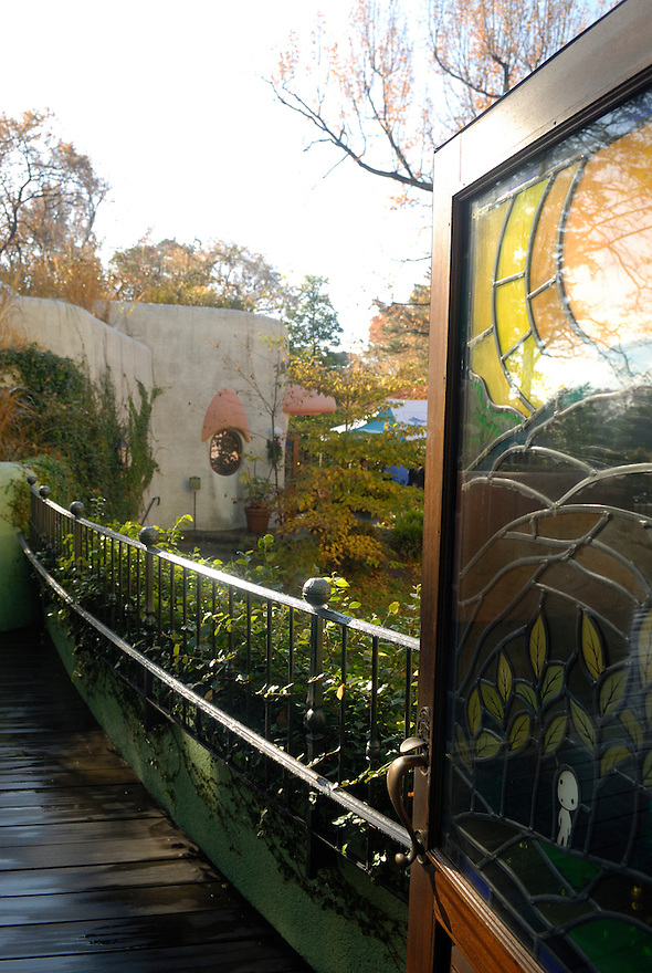 A stained glass panel in a door opening out onto one of the museum's many walkways. The Ghibli Museum in Mitaka, western Tokyo opened in 2001. It was designed by animator Miyazaki Hayao and receives around 650,500 visitors each year.